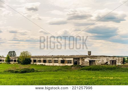 Old abandoned dilapidated agricultural building. Collapsing facade.