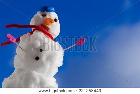 Little happy christmas snowman in blue screw top as hat red scarf and pink gloves outdoor. Winter season seasonal specific. Blue sky background.