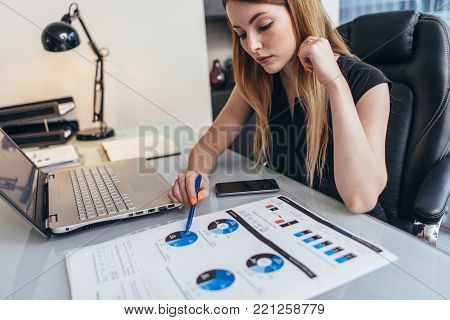 Female businesswoman readind financial report analyzing statistics pointing at pie chart working at her desk.