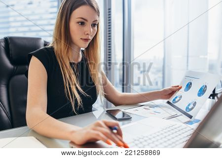 Female director working in office sitting at desk analyzing business statistics holding diagrams and charts using laptop.
