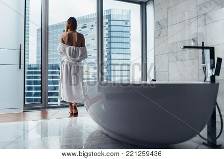 Back view of young woman wearing white bathrobe standing in bathroom looking out the window with bathtub in foreground.