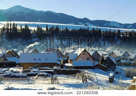Winter rural landscape - mountain village covered with snow misty morning. Habovka, Western Tatras, Slovakia, Orava region. Travel destination for winter vacations and skiing.