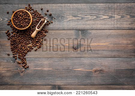 Fresh roasted coffee beans in bowl and scoop on dark wooden table top view copy space. Coffee background