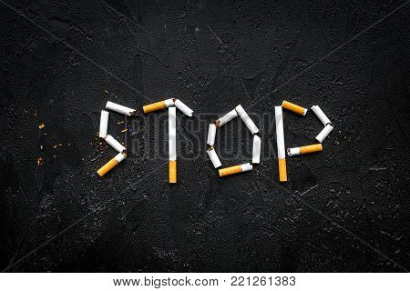 Stop smoking. Word stop lined cigarettes on black background top view.