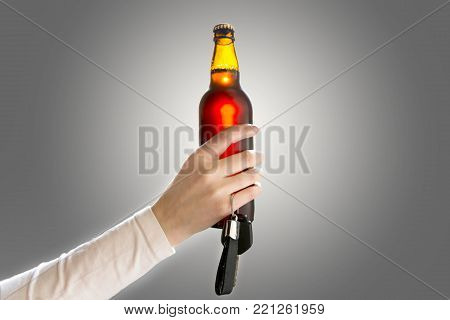 Woman's hand holding bottle of beer and car keys. Do not drink and drive concept