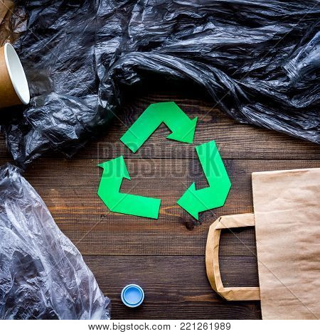 Green paper recycling sign among waste materials paper, plastic, polyethylene on dark wooden background top view.