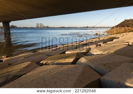 Details of a concrete walkway along the waterfront against a river dike overlooking the water and the delta