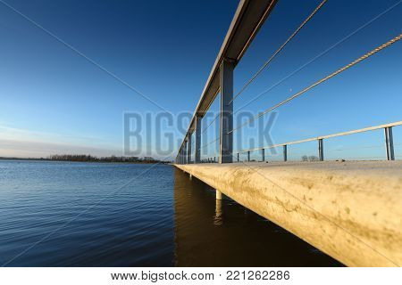 Details of a concrete walkway along the waterfront against a river dike overlooking the water and the delta. Empty bridge / walkway background with copy space