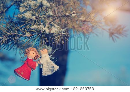 Two small dolls angels with sprig of pine sprinkled with snow. Christmas decorations and toys for Christmas tree. small red dolls angels. winter selebrations beautiful background. instagram filter.
