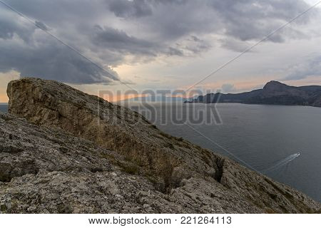 Cracks and rifts in the rocks. The peak of Cape Alchak. Summer, cloudy. Surroundings of Sudak, Crimea.