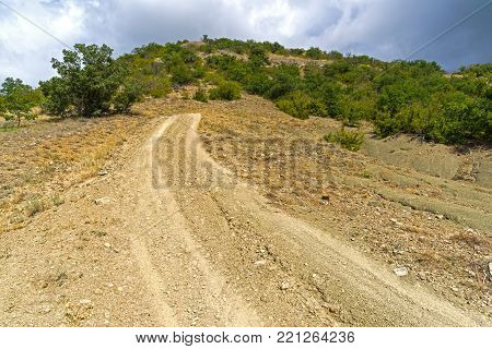 Steep descent on a dirt road. Crimean mountains.