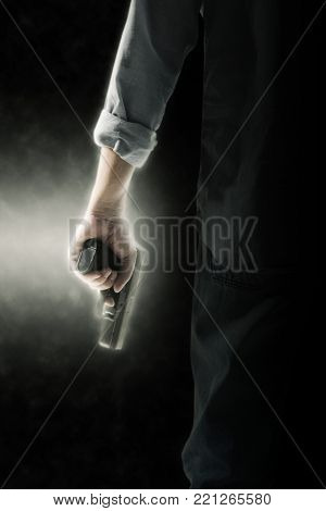 Man's hand holding a pointing gun with a finger on the trigger. Soft focus