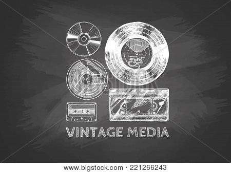 Media evolution set drawn with chalk on blackboard. Vinyl record, tape reel, compact tape cassette, VHS and compact disc.