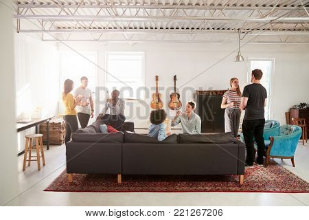 Friends at a party in a New York loft apartment, full length