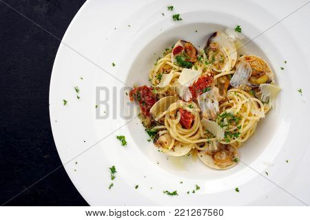 Spaghetti alle vongole with tomato pesto as top view on a plate with copy space left