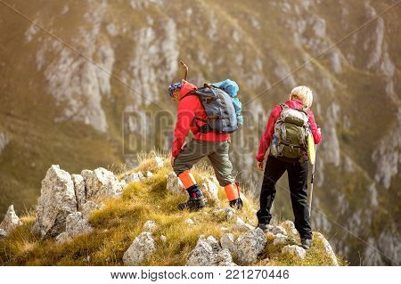 adventure, travel, tourism, hike and people concept - smiling couple walking with backpacks outdoors.