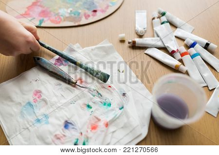 fine art, creativity and artistic tools concept - artist hand with paintbrush, palette knife, paper tissue and paint tubes