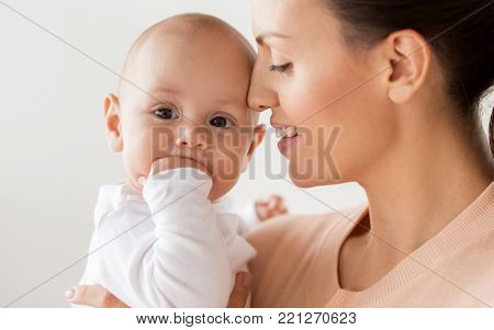 family, motherhood and people concept - close up of happy mother with little baby boy at home