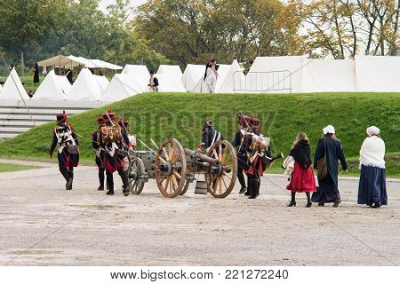 Napoleonic soldiers and their women are marching to a military camp. Napoleonic base with white tents.