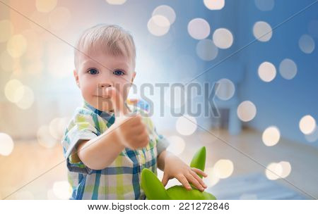 childhood, toys and people concept - happy little baby boy playing with ride-on toy horse and showing thumbs up at home