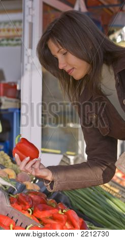 Image of a young woman in a vegetable market buying red peppers.Shot with Canon 70-200mm f/2.8L IS USM poster