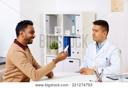 medicine, healthcare, medication and people concept - doctor and happy patient with nasal spray at hospital