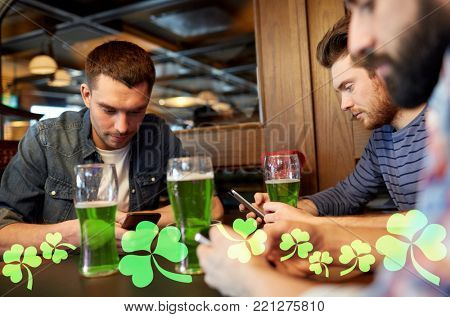 st patricks day, technology and leisure concept - male friends drinking green beer and messaging on smarphones at bar or pub