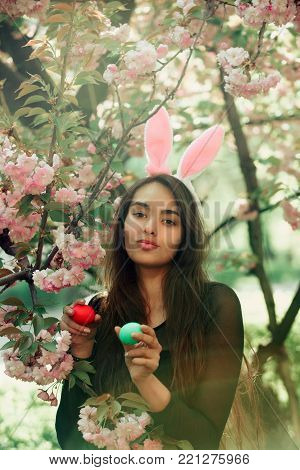 girl with rosy bunny ears and long, brunette hair holding colored eggs, green and red, at tree with blossoming sakura flowers on sunny day on floral environment. Easter. Spring