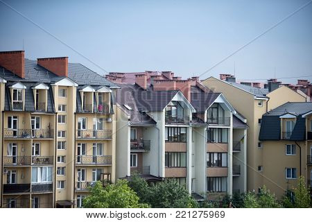 Houses with windows, balconies, roofs in residential district on blue sky background. Architecture, construction, structure, design. Real estate, dwelling, property concept.