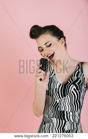Music, look and retro style, pinup. Girl in glasses sing in microphone. Pin up young girl on pink background, radio. Beauty and vintage fashion. Woman singer with stylish retro hair and makeup.