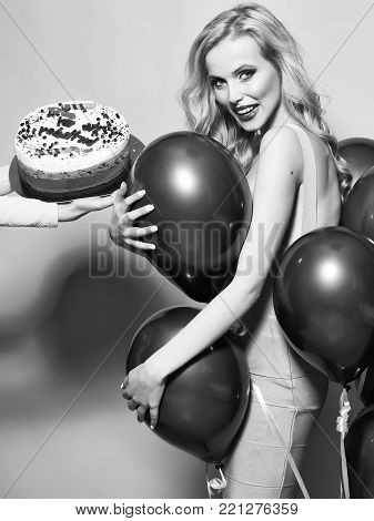 One attractive smiling young happy blond woman with long curly hair with birthday cake with candle in female hand near bunch of red party balloons in studio on yellow backdrop, vertical picture