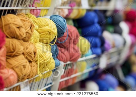 Variegated and bright pile of knitting yarn for knitting. Store of goods for creativity and needlework. Hobby, needlework, retail