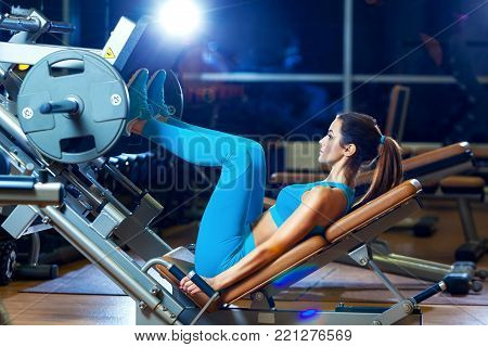 fitness, sport, bodybuilding, exercising and people concept - young woman flexing muscles on leg press machine in gym.