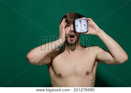 Man With Sexy Torso Hold Alarm Clock On Black Background