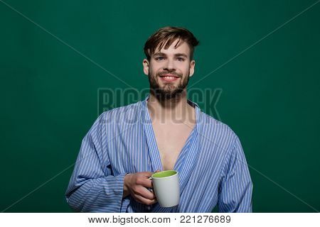 Happy man with cup on green background. Bachelor in blue dressing gown smile with mug. Morning routine concept. Breakfast, coffee or tea time. Hot drink, diet, health.