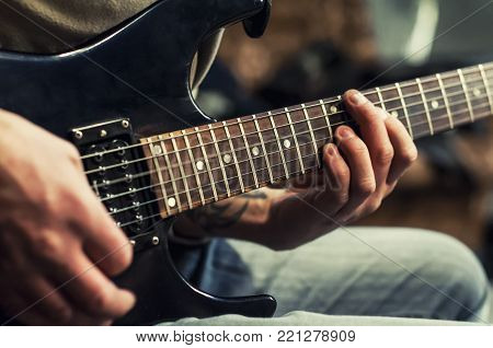 The hands of the rhythm guitarist. Closeup. Playing the guitar. Selective focus.