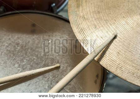 Drum sticks, a plate and a drum,volume. Playing on the drum kit drummer. close-up. Selective focus.