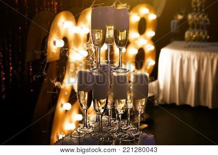 Glasses of champagne made in a pyramid for event party or wedding ceremony. Pyramid of glasses of champagne for celebrate in party with background of light bulbs, 2018
