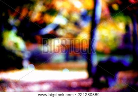 The abstract and blurred silhouettes and outlines of a colorful park landscape in autumn.