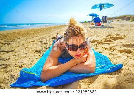 bored woman sad pensive lay down beach towel single loneliness sad lifestyle .