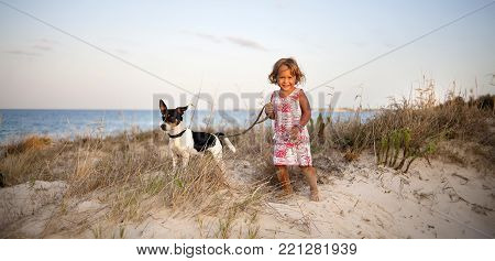 Panoramic photo of two years old  laughing girl holding Jack Russell dog on a leash on the beach