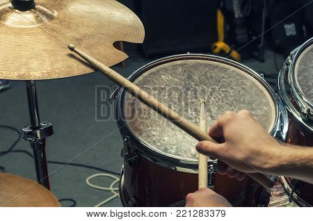Drum sticks, a plate and a drum (volume). Playing on the drum kit drummer. close-up. Selective focus.