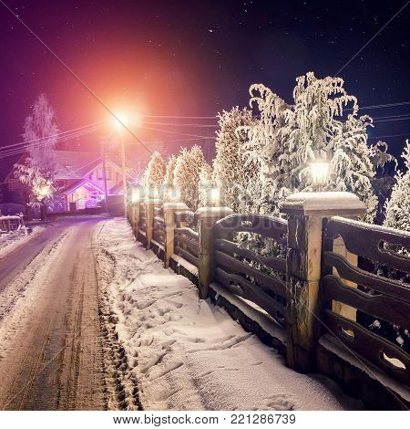 Winter night scene. starry sky over snowy road and mountain cottage, Christmas holidays, and tourism concept. rural winter landscape.
