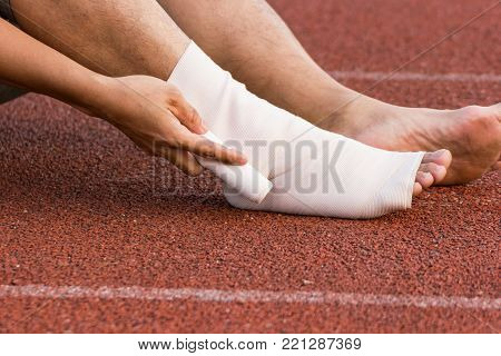 Male athlete applying compression bandage onto ankle injury of a football player, Sports injuries.