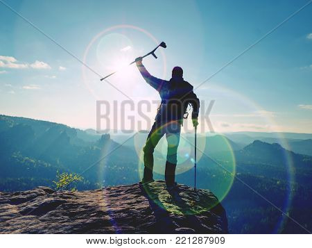 Tourist with  forearm crutch above head  on trail. Hurt hiker achieved mountain peak with broken knee in immobilizer.  Deep valley bellow silhouette of man. Early autumnal daybreak