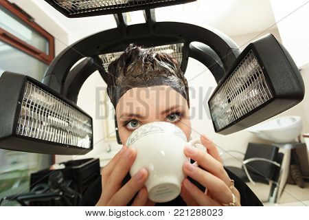 Young woman drinking coffee tea in hairdressing beauty salon. Girl dying colouring hair by hairdresser hairstylist. Modern equipment.