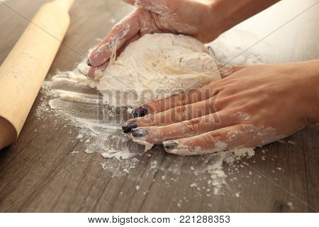 Woman hands knead the dough close-up. Home cooking background.