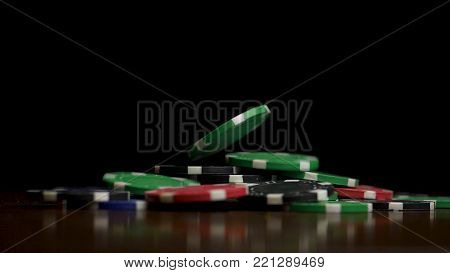 Falling poker chips isolated on black background. Falling poker chips isolated on black background. Colorful poker chips falling at the table on black background. Playing chips flying at the black background.