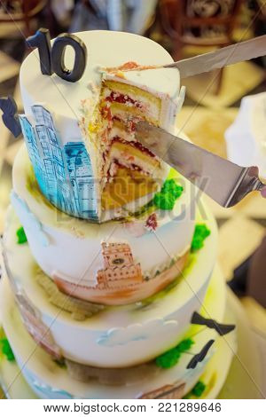 Big multilevel cake with decorative 10, buildings and church, knife and scapula