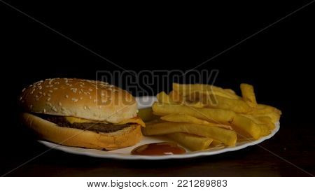Hamburger with fries isolated on black background. French fries on white plate with ketchup and cheese sauce isolated on black background. Top view.Chicken burger plate with french fries and salad.